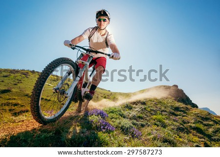 Mountain bike. Man riding bicycle on a dusty trail. Downhill. - stock photo