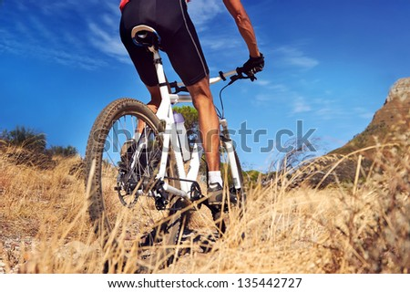 mountain bike man with blue sky riding on outdoor trail in nature - stock photo