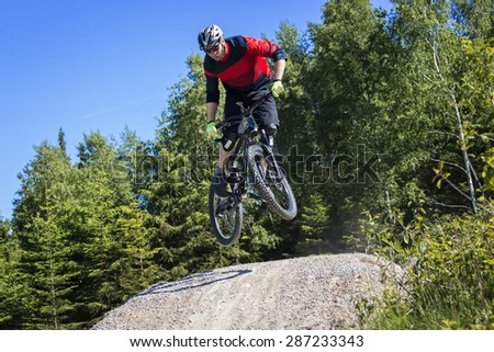 Mountain bike rider jumps over a dirt track kicker - stock photo