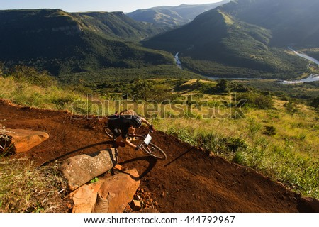 Mountain biker going downhill with a beautiful green valley with a river running through it.  - stock photo