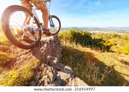 Mountain biker in action on rocks looking at downhill trail against blue sky concept for healthy lifestyle, exercise and extreme sports - stock photo