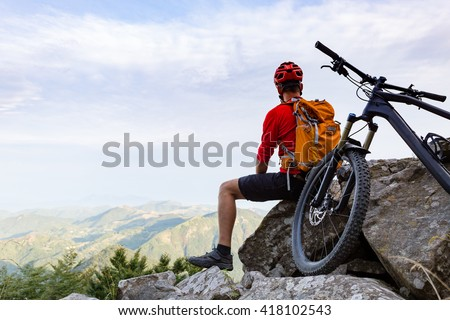Mountain biker looking at view on bike trail in autumn mountains. Male rider resting on cycling trip in nature. Sport fitness, motivation and inspiration in beautiful inspirational landscape. - stock photo