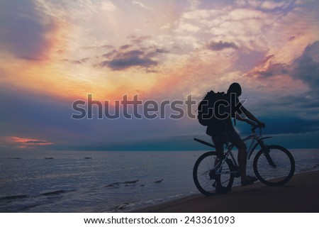 Mountain biker on beach and sunset, stormy sky  - stock photo