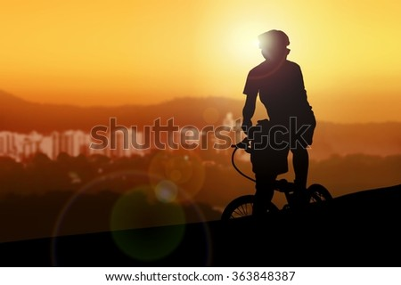 Mountain biker resting while watching sunset - stock photo