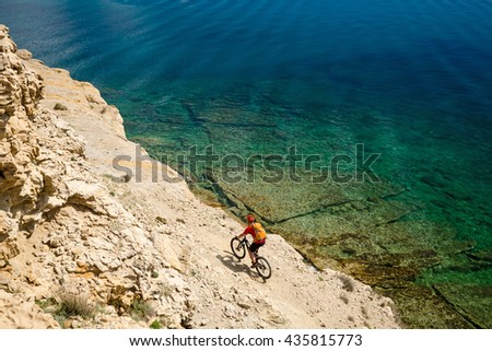 Mountain biker riding a bike at the seaside and mountains landscape. Man cycling MTB on enduro trail dirt path. Sport fitness motivation and inspiration in beautiful environment. - stock photo
