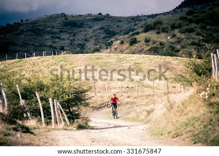 Mountain biker riding on bike singletrack trail in autumn mountains. Man rider cycling MTB on rural country road or single track. Sport fitness and inspiration in beautiful inspirational landscape. - stock photo