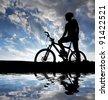 mountain biker silhouette in sunrise - stock photo