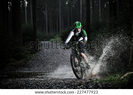 Mountain biker speeding through forest stream. Water splash in freeze motion. - stock photo