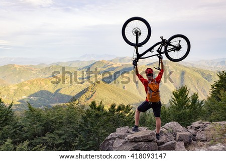 Mountain biker success, looking at view celebrating with bike up on trail in autumn mountains. Successful happy rider on rocks holding bicycle. Sport, adventure, motivation and inspiration. - stock photo