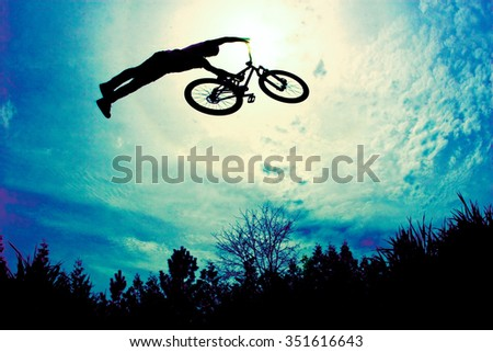 Mountain bikers does a superman off a jump - stock photo