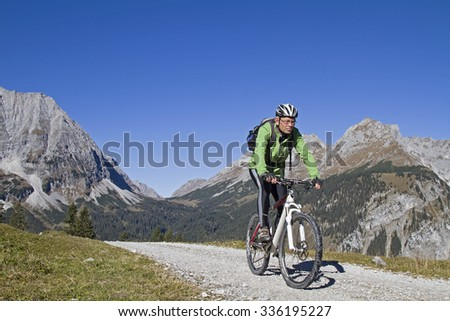 Mountain bikers on the way to the Falken hut in Karwendel mountains - stock photo