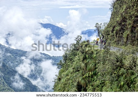 "Mountain bikers riding the famous downhill trail ""Road of death"" in Bolivia - stock photo"