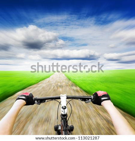 Mountain biking down hill descending fast. View from bikers eyes. Motion blurred - stock photo