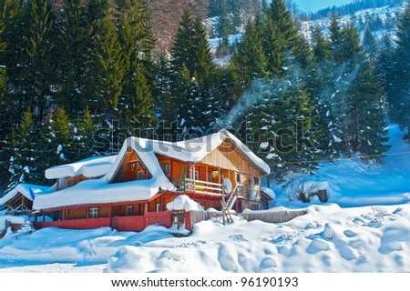 mountain chalet  covered snow  in winter - stock photo