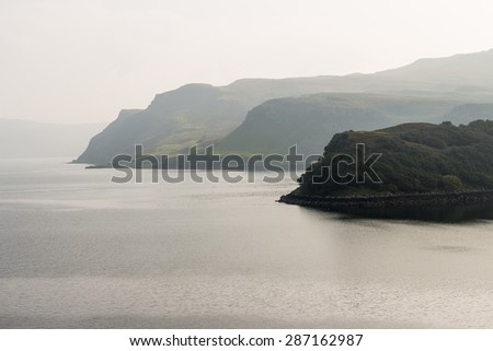 Mountain cliffs shrouded in fog over the ripples of a calm sea in the green coast of the isle of Skye, Scotland. The misty atmosphere and evocative views from Portree are relaxing and emotional. - stock photo