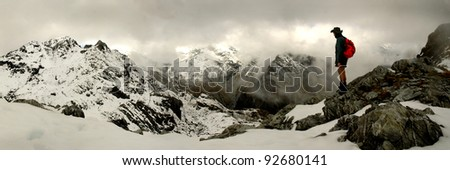 mountain climber looking over snowy peaks - stock photo