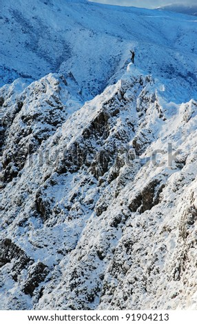 mountain climber on icy peak in mountains - stock photo