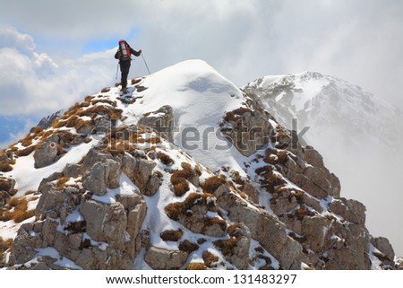 Mountain climber on top of the mountain in bad weather during winter - stock photo