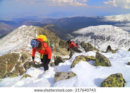 Mountain climbers on a steep ridge on snow covered mountain - stock photo