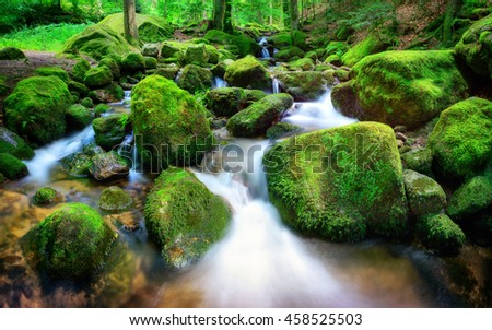 Mountain creek with clear water gently cascading down through moss covered rocks in soft light - stock photo