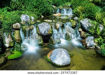 Mountain creek with waterfall - stock photo