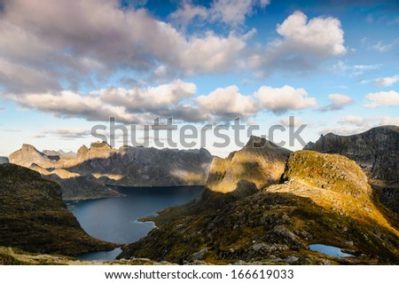 Mountain evening view in the middle of wild part of Lofoten islands, warm sunset light, Norway - stock photo