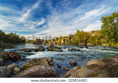 Mountain fast flowing river stream of water in the rocks with blue sky - stock photo