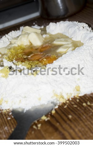 mountain flour with egg yolk on a wooden table. Preparation of a Neapolitan pastry. - stock photo