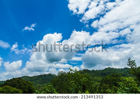mountain green field and blue sky with light clouds - stock photo