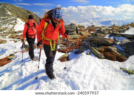 Mountain hikers on snow covered ridge in fine winter day - stock photo