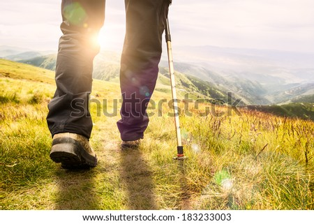 Mountain hiking.  Lens flare, shallow depth of field. - stock photo