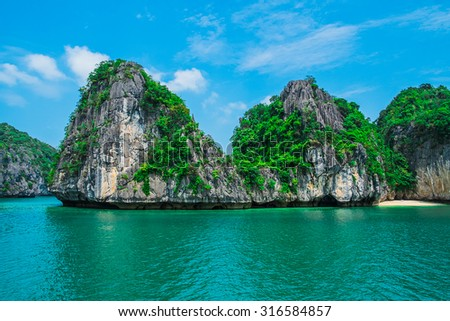 Mountain island and lonely beach in Halong Bay, Vietnam, Southeast Asia - stock photo