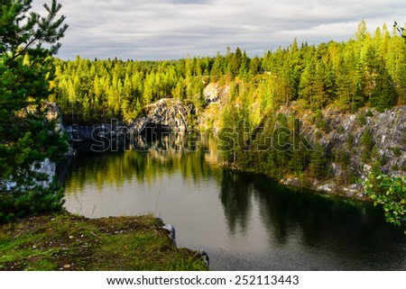 Mountain lake landscape surrounded with rocks and forest - stock photo