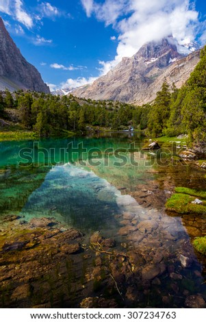 Mountain lake view vertical. Scenic landscape with vibrant water surface forest and high mountain peak blue sky  - stock photo