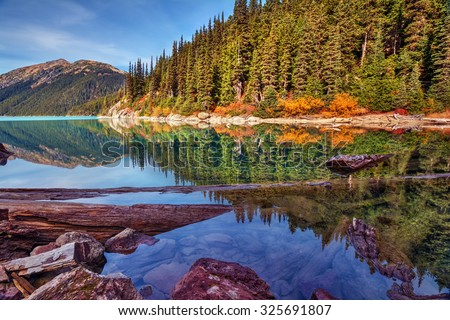 Mountain lake with a perfect reflection, varying shades of blue, and wooded shores - stock photo