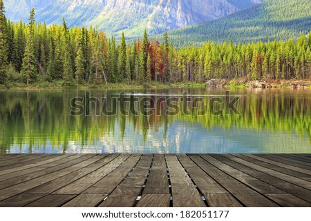 Mountain lake with wooden floor background (mooring). Jasper National Park, Rocky Mountains. Alberta, Canada  - stock photo
