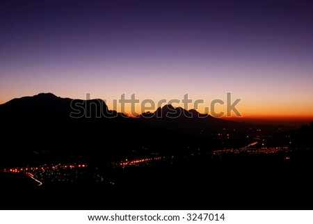 Mountain landscape at night in Franschhoek, South Africa, shot from the highest point above the town. - stock photo