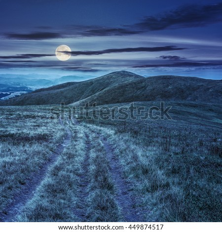 mountain landscape. curve path through the meadow on hillside at night in full moon light - stock photo