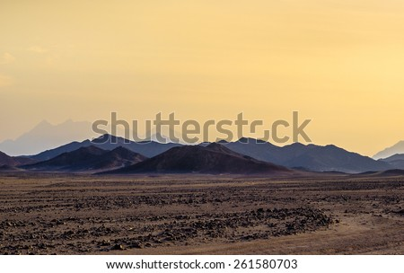 Mountain landscape in vibrant colors. Sunset at the hills in stone desert. Landscape with color mountainous silhouette. Scenic view of ridge mountains in Arabian desert. - stock photo