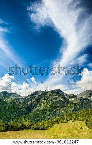 Mountain landscape of Retezat National Park in South Carpatians, Transylvania, Romania, Europe. Small lake with blue sky reflection at center. - stock photo