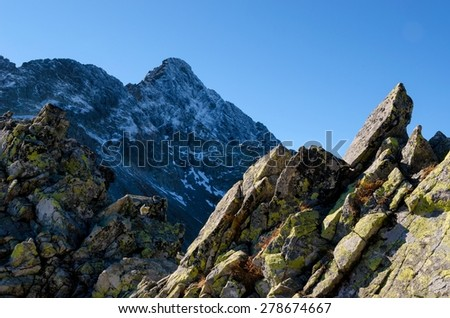 Mountain landscape. Picturesque view from the ridge over high peak covered with snow, Tatra mountains in autumn season. - stock photo
