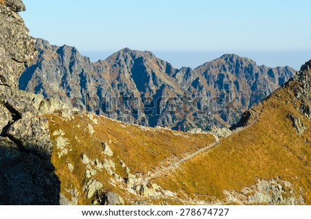 Mountain landscape. Picturesque view stretches over trail leading to the pass and rocky summits in Tatras National Park in autumn season. - stock photo