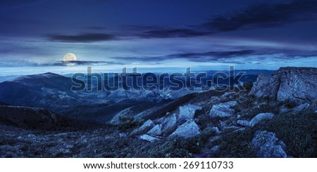 mountain landscape. valley with stones in grass on top of the hillside of mountain range at night in foll moon light - stock photo
