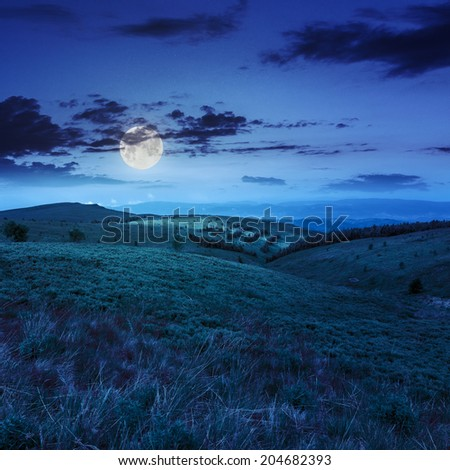 mountain landscape. valley with stones on the hillside. forest on the mountain under the beam of light falls on a clearing at the top of the hill at night in moon light - stock photo