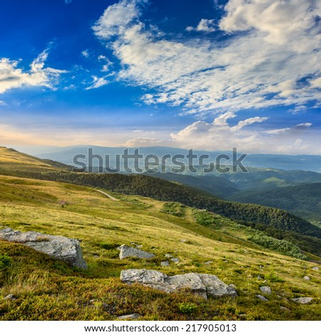 mountain landscape. valley with stones on the hillside. forest on the mountain under the beam of light falls on a clearing at the top of the hill at sunrise - stock photo