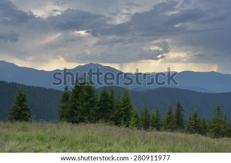 Mountain landscape with bad weather. Summer evening with rain over the top - stock photo