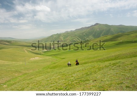 Mountain landscape with green grass valley and riders on horseback under white clouds sky - stock photo