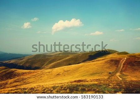 Mountain landscape with retro colors. Hills in summer time and remote off-road car near the dirt road - stock photo