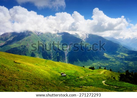 Mountain landscape with small wooden shack in green valley. White clouds on blue sky in summer day - stock photo