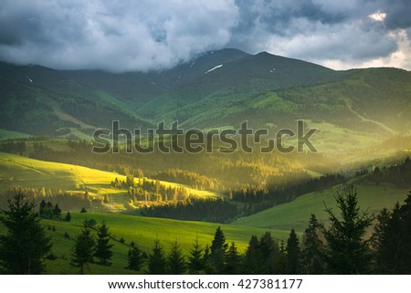 Mountain landscape with storm clouds. The sun's rays illuminate the meadow at sunset. - stock photo